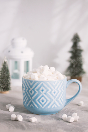Christmas and Happy New Year cozy composition blue mug with white pattern of cacao with marshmallows, candle lamp and fir-trees, gray concrete background. Xmas greeting card, winter holiday concept.