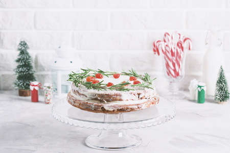 Christmas cake on glass stand decorated with rosemary and dried red berries. Winter holiday composition with candy canes, bottle of milk, candle lamp and fir-trees, colored sprinkling. Stok Fotoğraf - 114579960