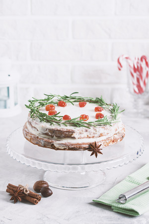Christmas cake on glass stand decorated with rosemary and dried red berries. Winter holiday composition with candy canes, bottle of milk, candle lamp and fir-trees, colored sprinkling. Stok Fotoğraf - 114579995