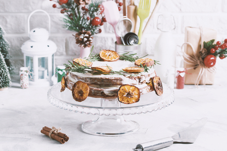 Christmas cake on glass stand decorated with rosemary and dried mandarin slices. Winter holiday composition cinnamon, gift box, metallic spoon, kitchen stuff tools. Stok Fotoğraf - 114579996
