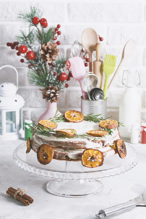 Christmas cake on glass stand decorated with rosemary and dried mandarin slices. Winter holiday composition cinnamon, gift box, metallic spoon, kitchen stuff tools.