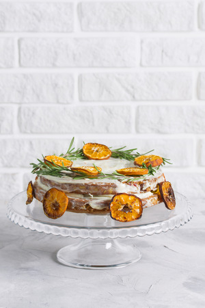 Cake on glass stand decorated with rosemary and dried mandarin slices on grey concrete white brick wall background. Vertical orientation, place for copy space. Imagens - 114579998