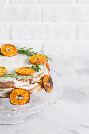 Cake on glass stand decorated with rosemary and dried mandarin slices on grey concrete white brick wall background. Close up, vertical orientation, place for copy space.