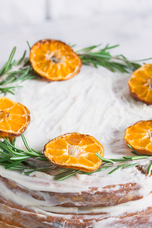 Cake on glass stand decorated with rosemary and dried mandarin slices on grey concrete white brick wall background. Close up, vertical orientation. Stok Fotoğraf - 114580000