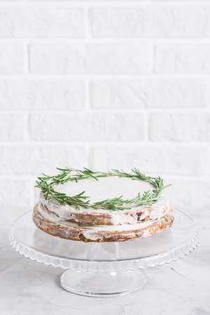 Cake on glass stand decorated with sprigs of rosemary on grey concrete white brick wall background. Vertical orientation, place for copy space.