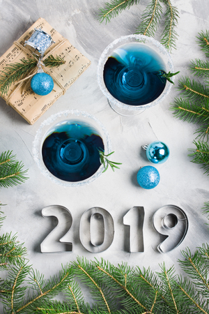 New year composition 2019 letters, martini drink with rosemary and sugar decoration, fir-trees, 