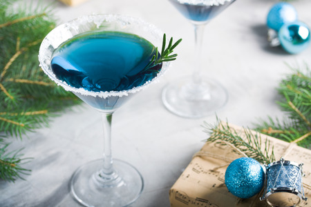 Christmas composition with martini drink with rosemary and sugar decoration, fir-trees, balls, 