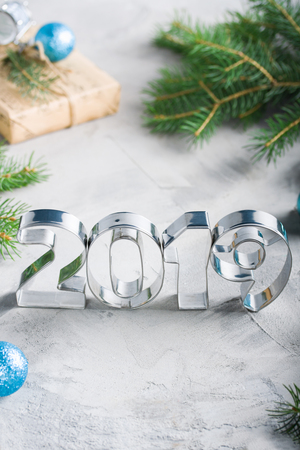 Happy New Year 2019 composition with metallic letters, balls, fir-tree, craft gift box in blue 