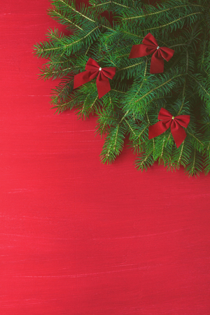 Red Christmas background with green tree bows on wooden background. New Year merry xmas winter holiday greeting card. Minimalism style flat lay top view place for copy space. Imagens - 114580031