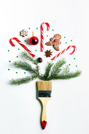 Draw me Christmas creative concept. Christmas new year winter holiday composition wooden brush fir tree branches ball gift box ginger man cookie candy cane hearts spruce. Flat lay top view copy space.