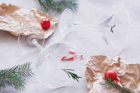 Christmas party over finish composition with empty martini glasses, craft gift wrapping, fir-trees, balls, broken candy canes, gray concrete background. Winter holiday, New Year party concept.