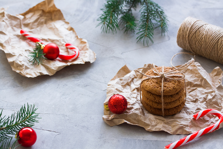 Oatmeal cookies tied with string in craft paper, skein of thread, balls, fir-trees branches, gray concrete background. Winter holiday, Christmas, New Year gift prepare concept. Imagens