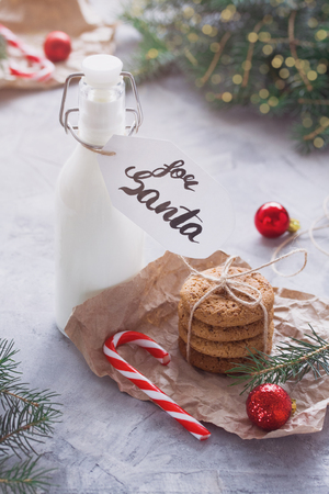 Milk in glass bottle and oatmeal cookies tied with string in craft paper for Santa Claus, skein of thread, candy canes, balls, fir-trees branches, gray concrete background. Winter holiday concept.