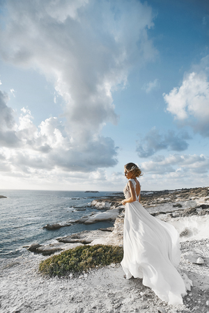 Beautiful young blonde model girl, in white dress, stands half sideways at the coast and looks at the sea