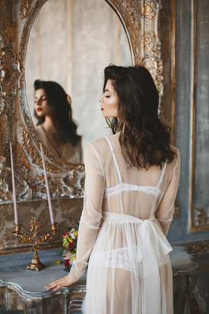 Sexy and beautiful brunette, young model woman, wearing in peignoir, stands in front of a mirror