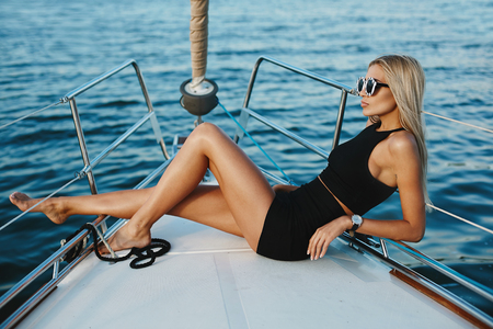 Beautiful fashionable blonde girl in black posing on a yacht ship