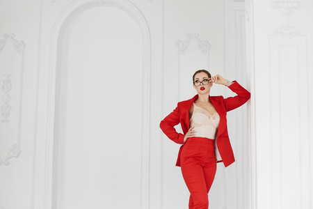 Sexy business lady wearing glasses and red suit posing in vintage interior 写真素材
