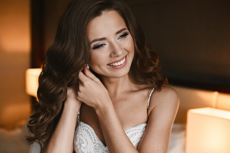 Portrait of happy, beautiful and fashionable brunette model girl with professional bright makeup and hairstyle, in lace dress posing and adjusting earring, wedding preparation of young bride