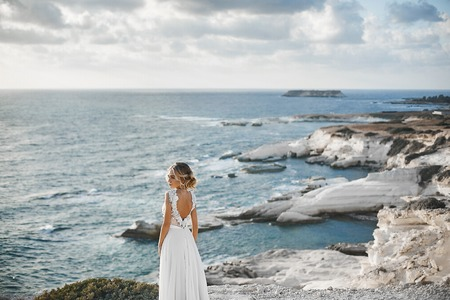 Beautiful young blonde model girl, in white lace dress with naked back, stands half sideways at the coast and looks at the sea.