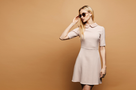 Beautiful and elegant young model blonde lady in fashionable sunglasses and beige short dress, with gold earrings posing in studio, isolated at background.