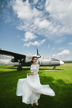 A young beautiful brown-haired bride, fashionable model girl in white dress runs holding the hem of her dress in front of the airplane. Reklamní fotografie
