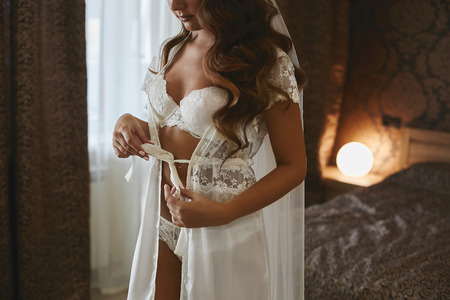 Amazing halfnaked beauty, sexy and sensual brunette model girl with long curly hair in lace lingerie unties a bow on her dressing gown, undress and posing in interior