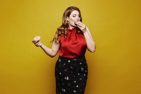 Plus size model, fashionable blonde girl with bright makeup, in red satin blouse and black skirt, with donuts in her arm posing with closed eyes in studio at yellow background.
