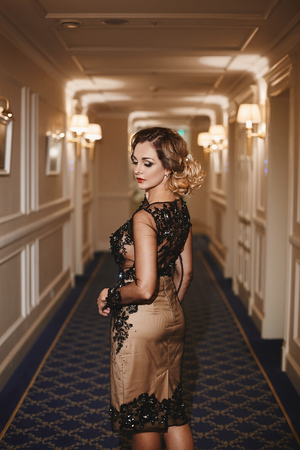 Sexy and fashionable young business lady with trendy hairstyle and with bright makeup, in stylish dress stands at the hall, looks back and posing at luxury vintage interior.