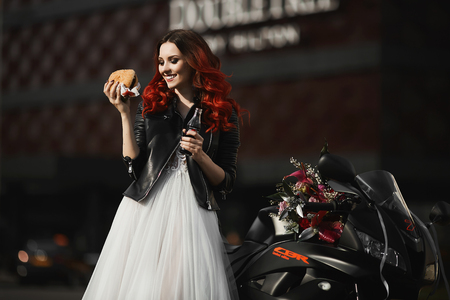 Fashionable, happy and smiling model girl with red hair and bright makeup, in a white wedding dress and in a leather jacket, with burger and cola in her hands, posing near sportbike Фото со стока
