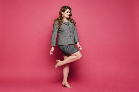 Plus size sexy model girl, fashionable blonde with bright makeup and with stylish hairstyle, in the skirt with geometric patterns and in a jacket posing in full length at the pink background in studio