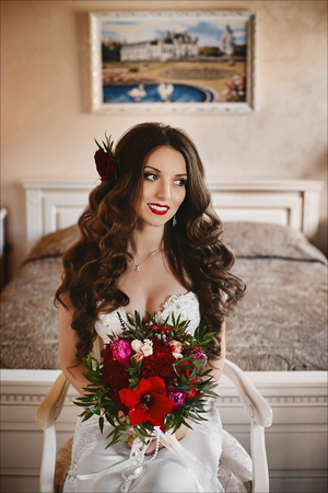 Fashionable and beautiful brunette model girl with bright makeup and with a shiny smile, in a white wedding dress and with a big luxury bouquet of exotic flowers in her hands posing at interior Фото со стока