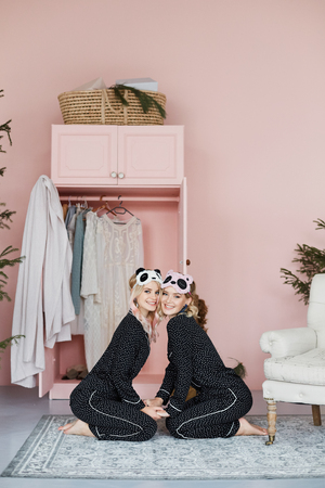 Two beautiful, happy and smiling blonde model girls in fashionable pajamas and in stylish sleeping masks in the form of pandas sit on the floor and posing at interior Stok Fotoğraf