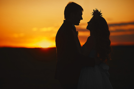 Silhouette of a couple of lovers at the sunset, beautiful blonde model girl with curly hair and with a floral wreath on her head and the young man in stylish suit posing at the sunset 스톡 콘텐츠