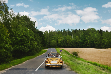 Golden retro cabriolet with a couple of just married, on the empty road between the field and the forest Archivio Fotografico