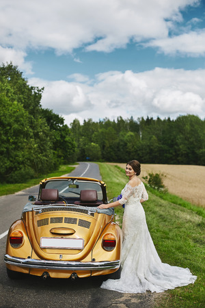 Young beautiful bride in a fashionable lace dress with a bouquet of blue flowers in her hands posing near the cabriolet retro car gold color