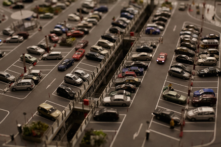 Miniature models figure cars and trucks at the big city parking.