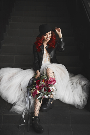 Fashionable model girl with red hair and beautiful smile in a white wedding dress and in a leather jacket, with a big and luxury bouquet of exotic flowers in her hands 版權商用圖片