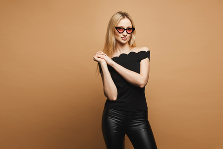 Beautiful blonde model girl with sexy body in black trendy leather pants, in a black blouse and in fashionable pink sunglasses at the orange background, isolated