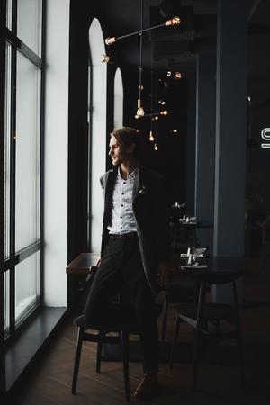 Stylish handsome businessman in fashionable coat at restaurant interior