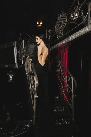 Fashionable and brunette model girl with perfect body and red lips in black evening dress with back posing at modern luxury interior