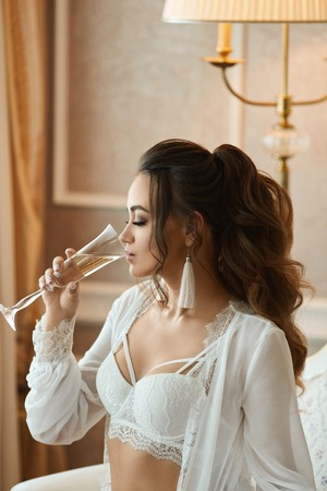 Sexy brunette woman with perfect body and with wedding hairstyle in a fashionable lace bra and in stylish peignoir drinking champagne at luxury vintage interior