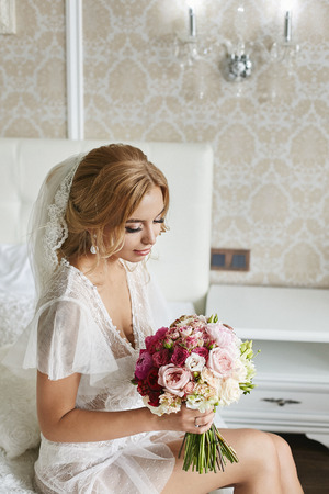 Sexy young blonde woman with wedding hairstyle in fashionable lingerie and in stylish peignoir with a bouquet of flowers in her hands at luxury vintage interior