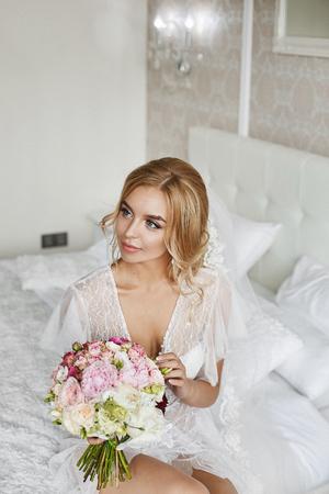 Sexy young blonde beauty with wedding hairstyle in fashionable lingerie and in stylish peignoir with a bouquet of flowers in her hands at luxury vintage interior