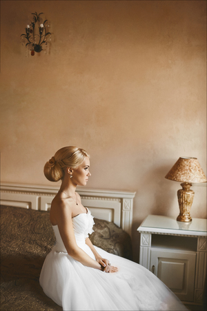 Young blonde beautiful woman with a perfect body and with stylish wedding hairstyle in a white dress sits on the bed at the bedroom