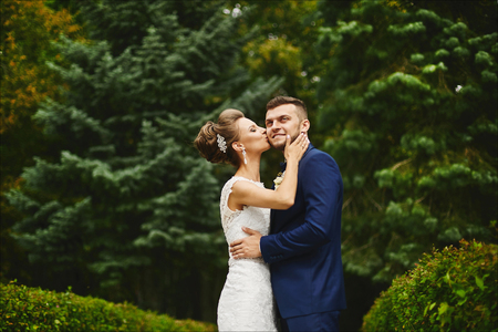 Beautiful young woman with perfect body and wedding hairstyle in lace dress hugs and kissing a handsome brutal man in the stylish blue suit outdoors at green park