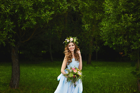 Young happy beauty with the wreath of fresh flowers on her head in trendy dress holding a bouquet of flowers in hands and posing outdoors at green park