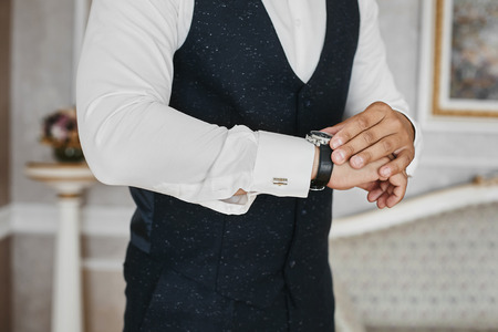 Close view of the luxury watches on the hand of a handsome businessman in a tuxedo and in a shirt with cufflinks