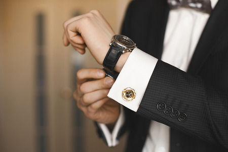 Close view of the luxury watches on the hand of a handsome businessman in a tuxedo and in a shirt with cufflinks.