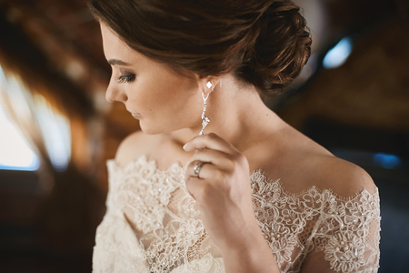 Young brunette beauty with wedding hairstyle in fashionable lace dress adjusting her earring and posing at interior