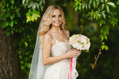 Bouquet of fresh flowers in the hands of the young beautiful woman with blond hair and in the wedding dress